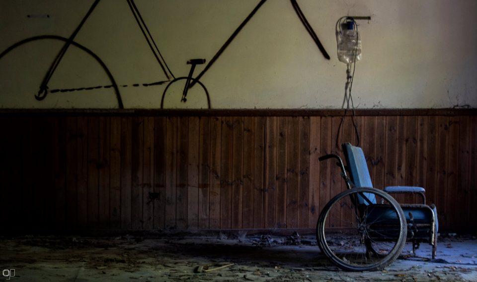 vecchia sedia a rotelle con flebo in stanza di manicomio