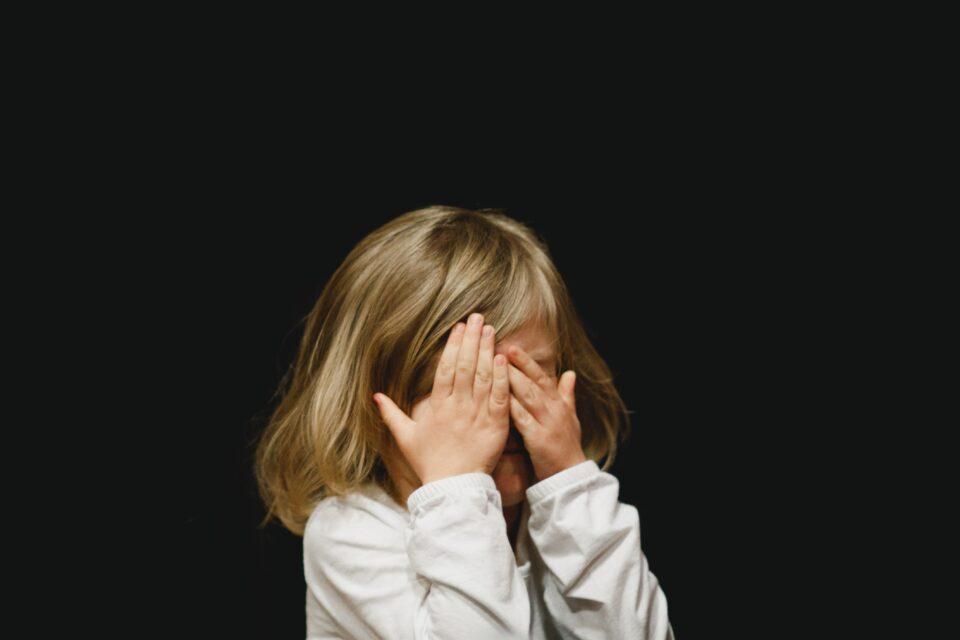 bambina che si copre gli occhi con le mani