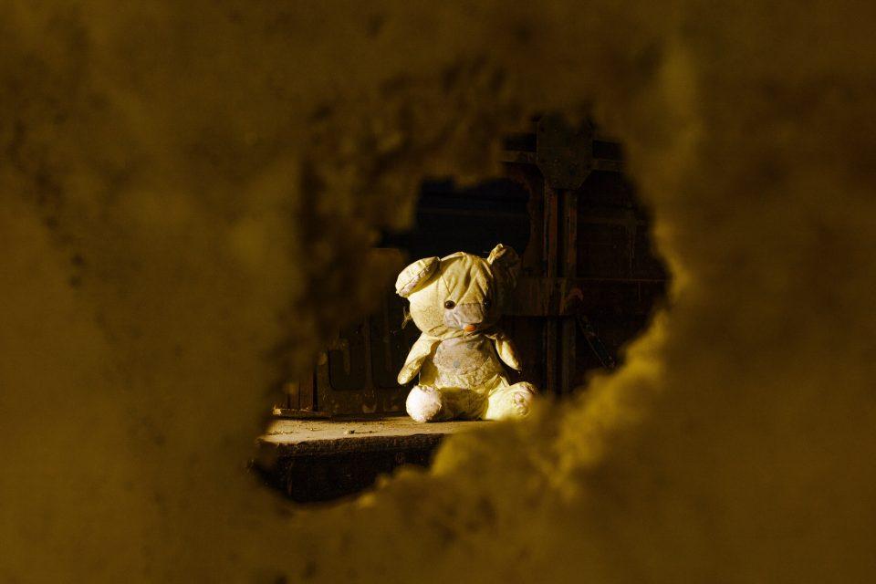 peluche sdrucito attraverso buco nella parete