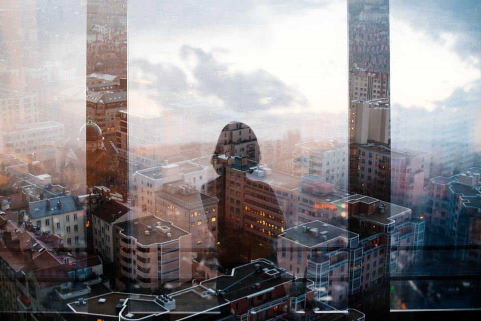 riflesso di donna sulla vetrata di un grattacielo