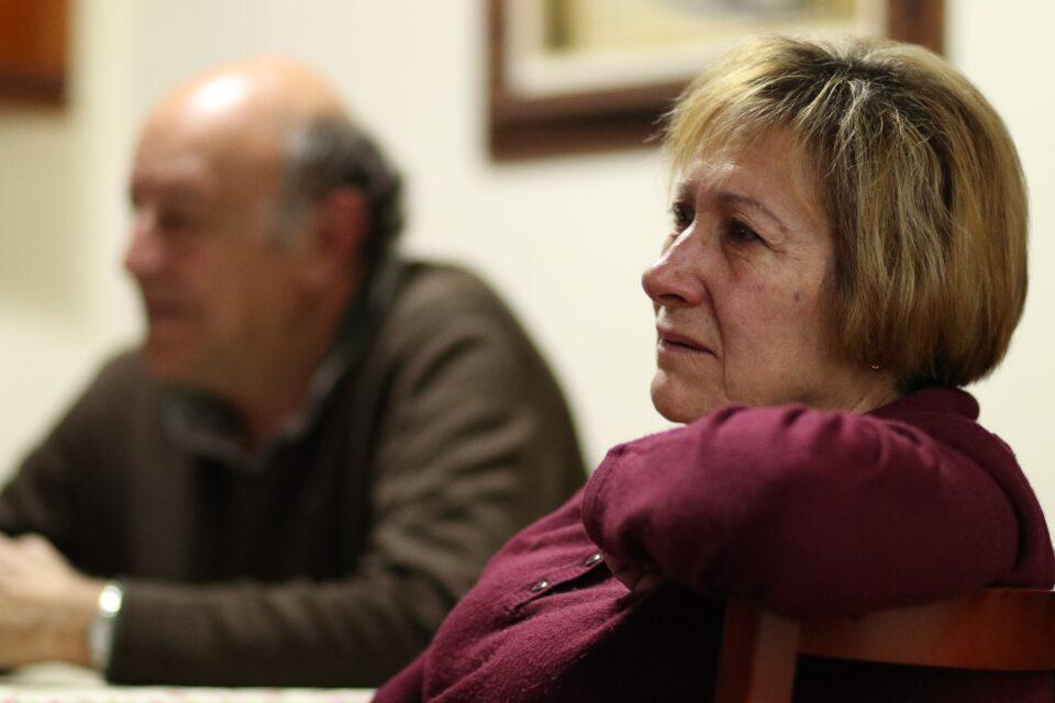 Madre che osserva con aria preoccupata e dolore e marito sullo sfondo